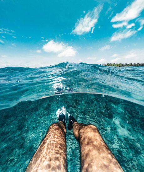 Pov view of man's legs in a clear water - Maldives - Split view hald underwater half overwater