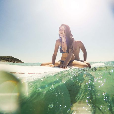 Love Couple surfing the waves and have a great time at summer holliday